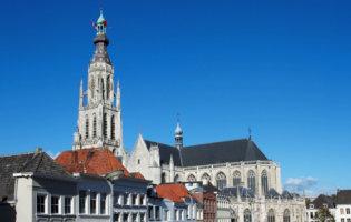 Foto Van Grote Kerk Breda Met Huizen Op De Voorgrond.
